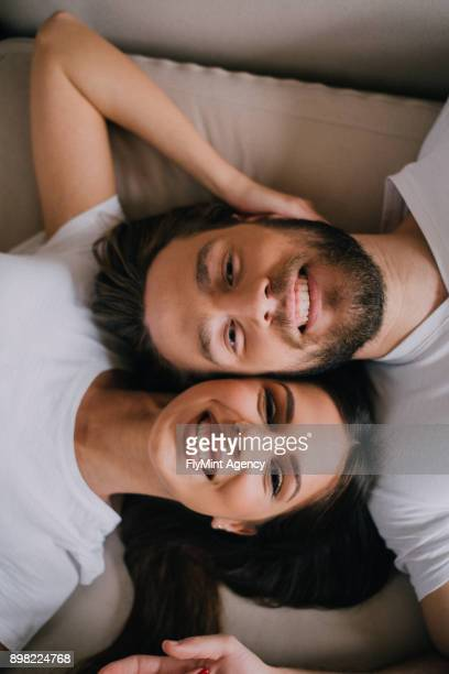 Beautiful couple lying cheek to cheek on a bed.