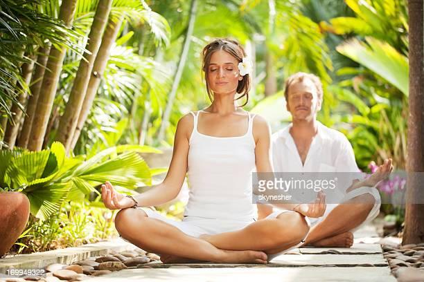 Beautiful couple meditating in the tropical surroundings