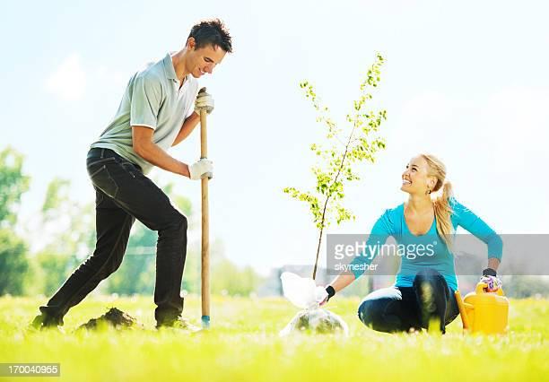 Beautiful couple planting a tree.