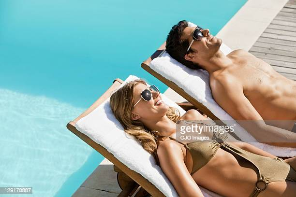 Beautiful couple relaxing on deck chairs near pool