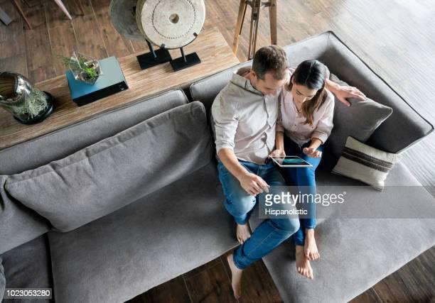 beau couple de détente sur le canapé en regardant une application sur tablette - couple photos et images de collection