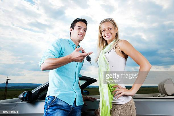 Beautiful couple showing keys of the car they bought.