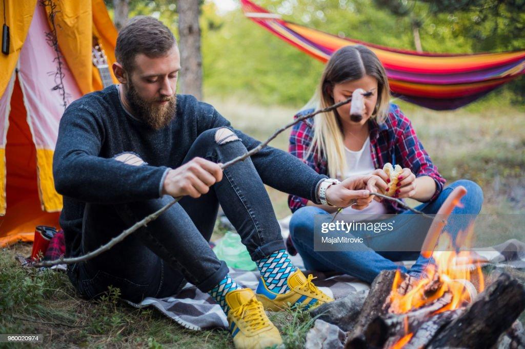 Schönes paar, sitzen, camping am Lagerfeuer. Auf dem Hintergrund mit einem Zelt schlägt der Mann das Feuer mit einem Stock. : Stock-Foto