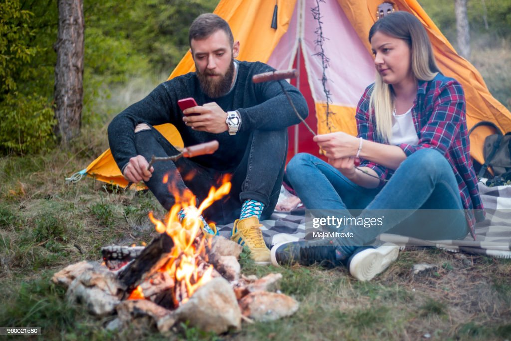 Beautiful couple, sitting, camping around the campfire. On the background with a tent The man flicks the fire with a stick. : Stock Photo