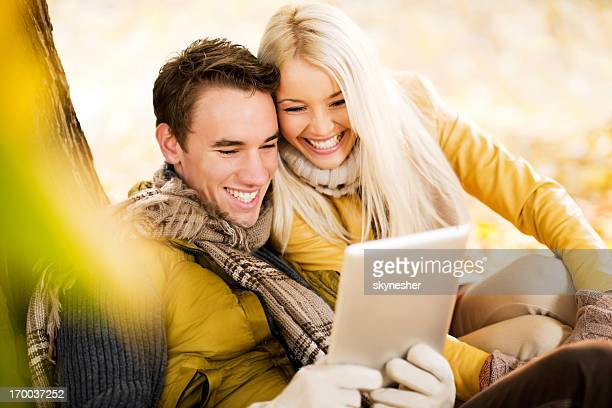 Beautiful couple sitting in park and using tablet computer.