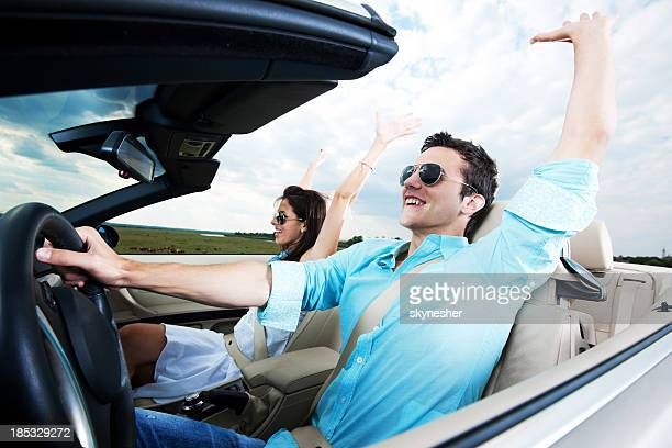 Beautiful couple sitting in their Convertible car with raised ha