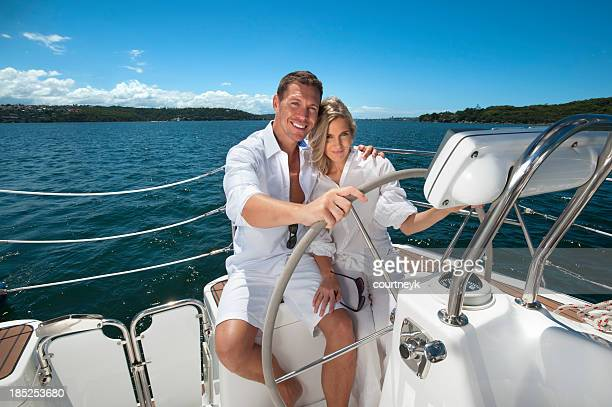 Beautiful couple steering sailing boat