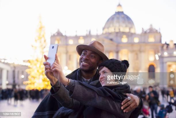 beautiful couple taking selfie at st. peter's square, rome - natale di roma foto e immagini stock