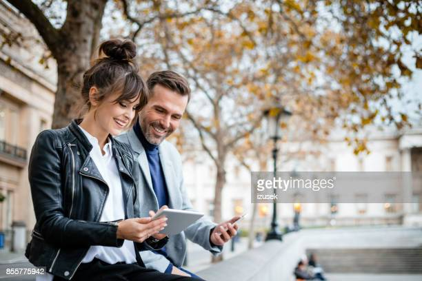 beautiful couple using digital tablet at trafalgar square in london, autumn season - a fall from grace stock pictures, royalty-free photos & images