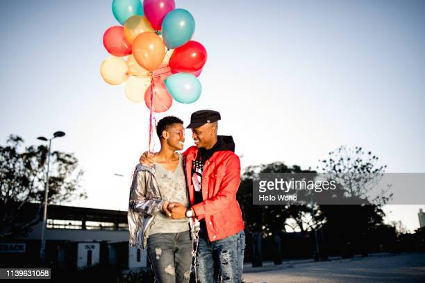 beautiful couple walking affectionately with balloons in hand - imágenes fotografías e imágenes de stock