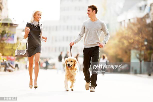 Beautiful couple walking the dog.