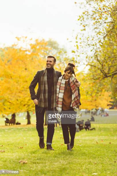 beautiful couple walking together in a public park - hyde park london stock photos and pictures