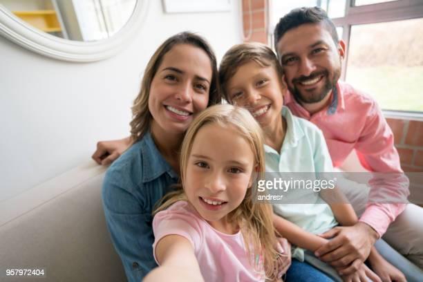 Beau couple avec leurs deux enfants détente à la maison assis sur le canapé en prenant un selfie tous les regardant sourire caméra