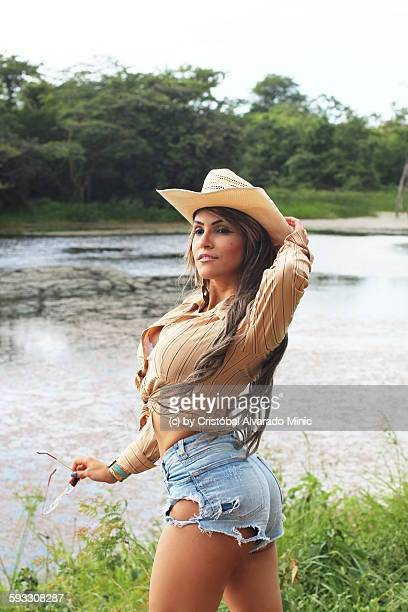 a beautiful cowgirl at the border of a lake - cowgirl hairstyles stock photos and pictures