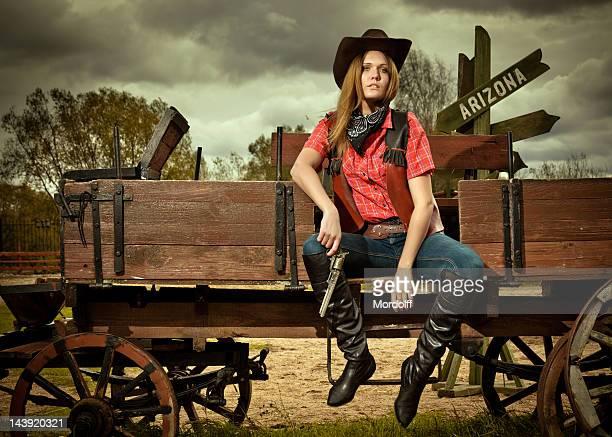 belle cowgirl avec arme à feu sur un chariot de cowboy - cowgirl photos et images de collection