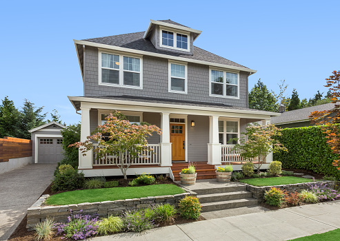 Beautiful craftsman home exterior on bright sunny day with green grass and blue sky 1222625117