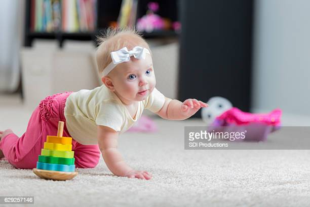 beautiful crawling baby girl - tapijt stockfoto's en -beelden