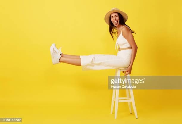 belle, jeune femme folle avec le chapeau de paille s'asseyant sur le devant blanc de chaise du fond jaune. - chapeau photos et images de collection
