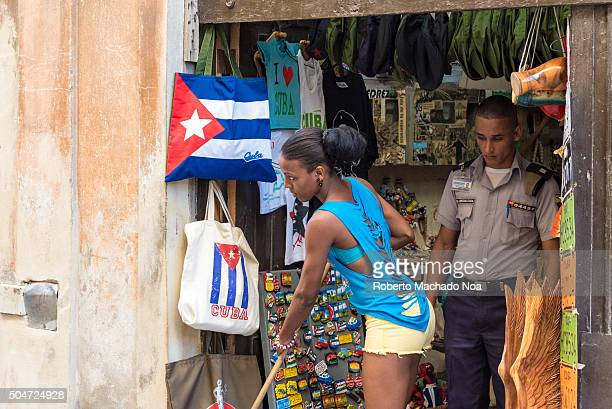 Beautiful Cuban woman and the police officer in Old Havana Girl owner of a small private business cleans the entrance while the police officer look...