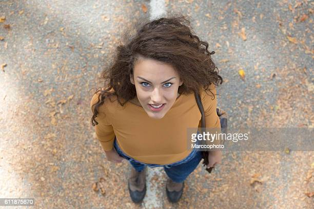 Beautiful curly girl with big blue eyes. Directly above view.