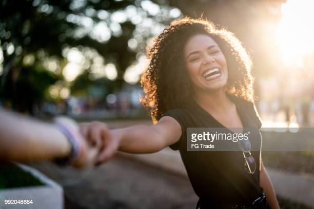 beautiful curly hair woman holding hands/following boyfriend - allegro foto e immagini stock