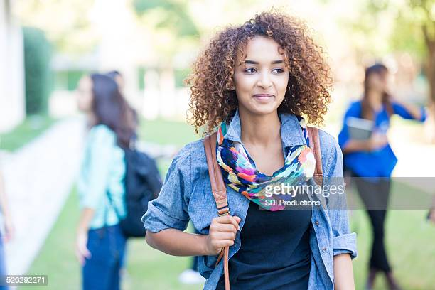 beautiful curly haired african american college or high school student - beautiful black teen girl stock photos and pictures