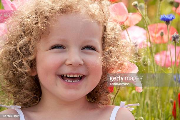 Beautiful curly haired toddler girl sitting on poppy field