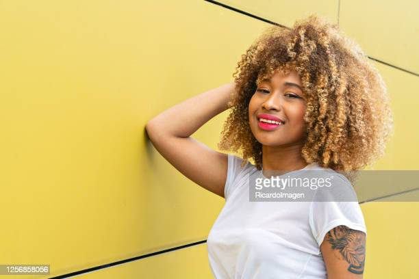 beautiful curly latina woman smiles on the street wearing casual clothes leaning against a yellow wall - natural black hair stock pictures, royalty-free photos & images