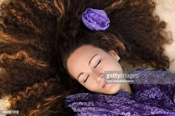 Beautiful curly woman with purple flower