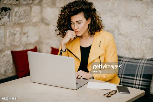 Beautiful curly-haired blogger is writing an article on a laptop in the cafe