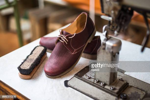 Beautiful custom made leather shoes next to sewing machine.