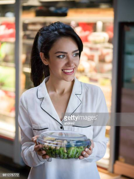 beautiful customer at a food store holding a salad and looking away daydreaming - convenience store stock photos and pictures