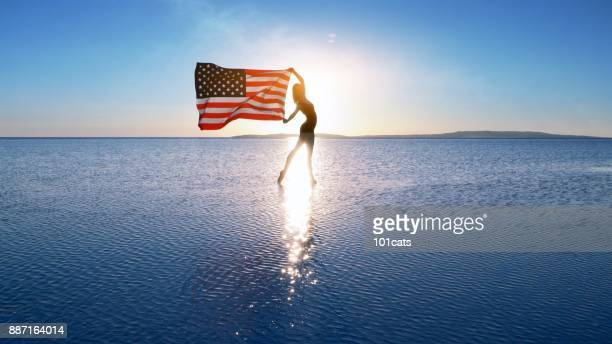 Beautiful dancer holding a US flag on the lake.