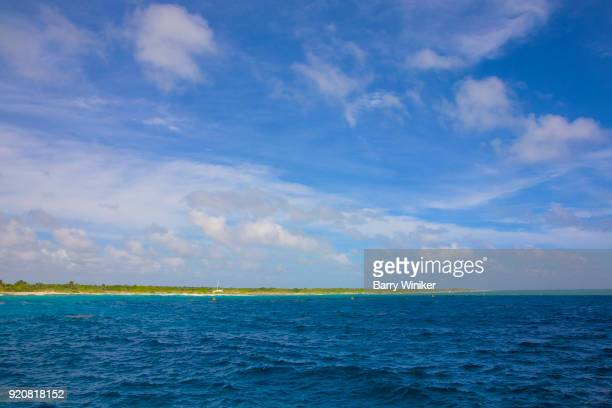 Beautiful dark blue color to Caribbean Sea under blue and white sky near shoreline of the Yucatan, Mexico
