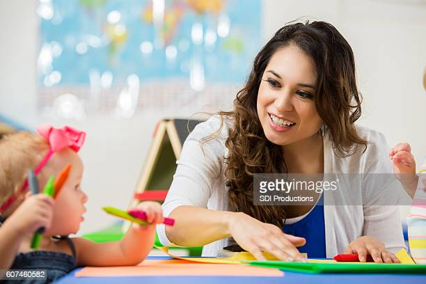 Beautiful daycare teacher helps toddler with coloring project