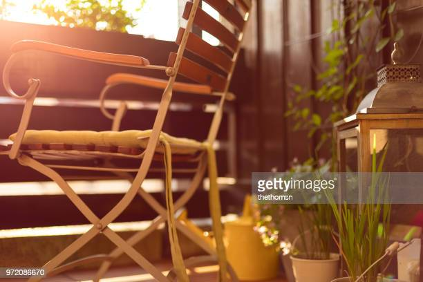 beautiful decorated balcony with chair, potted plants, lantern and watering can during sunset, germany - balkon stock-fotos und bilder