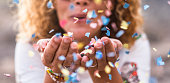 beautiful defocused woman blow confetti from hands. celebration and event concept. happiness and colored image. movement and happiness having fun