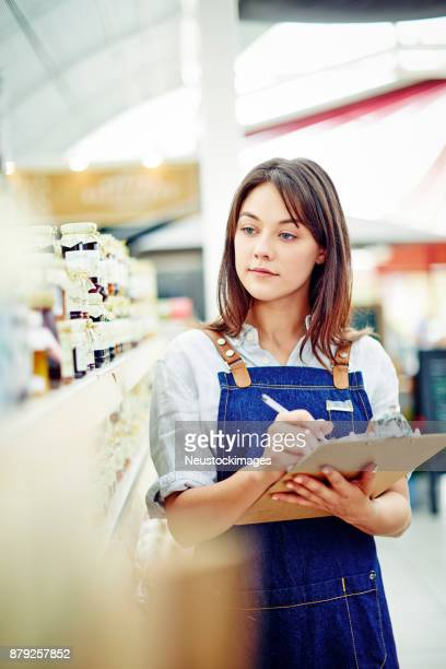 Beautiful deli owner holding clipboard and pen by shelves