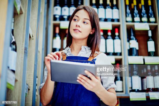 Beautiful deli owner holding digital tablet at alcohol section