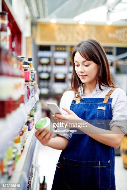 Beautiful deli owner scanning label on food container
