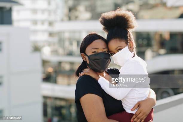 beautiful & delighted daughter and mother wearing black and white face masks on a rooftop - family stock pictures, royalty-free photos & images