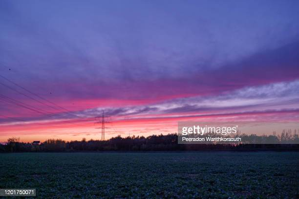 beautiful dramatic purple and pink cloud and sky after storm and raining over agricultural field and on countryside in germany. phenomenon of sky turn pink. nimbostratus cloud during sunset. - light natural phenomenon stock pictures, royalty-free photos & images