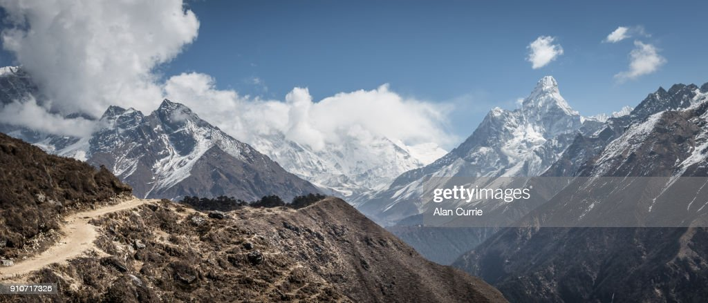 Beautiful dusty winding path with Mount Everest in the background, and deep valleys : Stock Photo