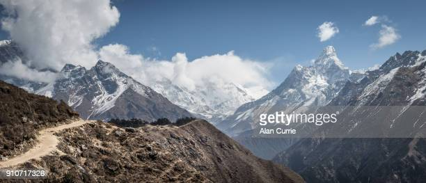 Beautiful dusty winding path with Mount Everest in the background, and deep valleys
