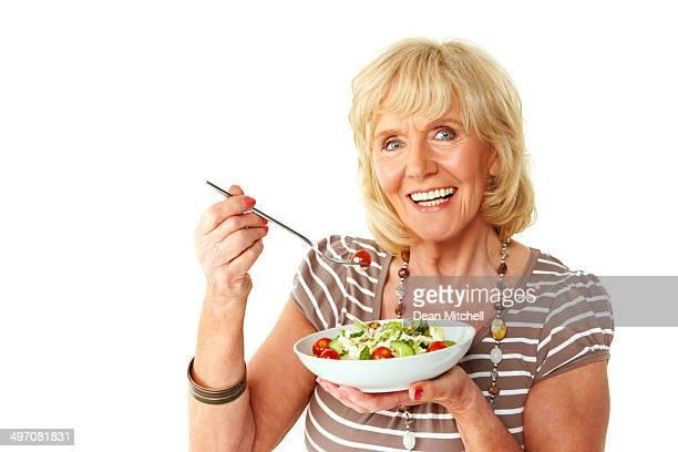 Bellissimo anziani donna che mangia una fresca e salutare insalata