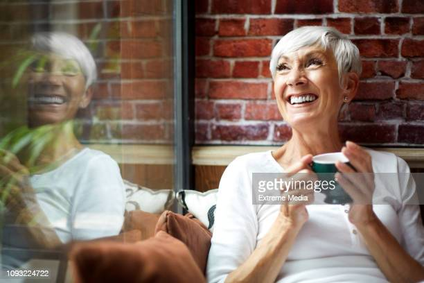 beautiful elderly woman having a nostalgic moment while drinking a hot drink from a cup - coffee drink stock pictures, royalty-free photos & images