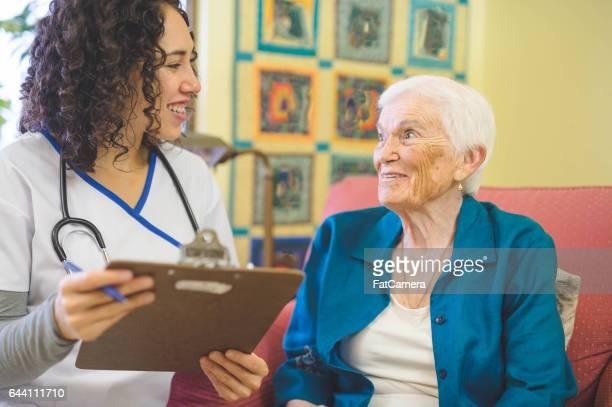 Beautiful elderly woman in apartment interacting with young Hawaiian nurse