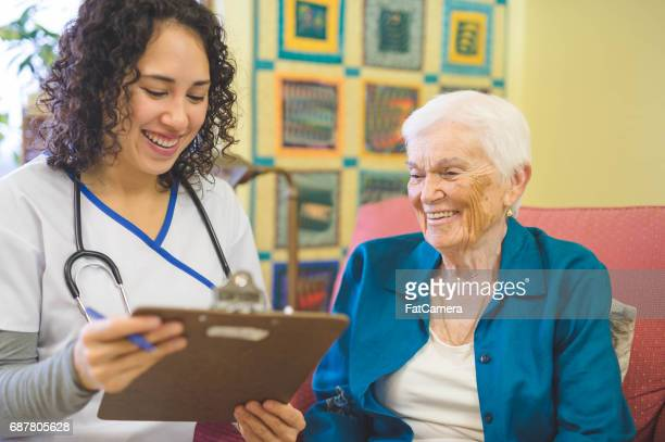 beautiful elderly woman in apartment interacts with young hawaiian nurse - nursing assistant stock photos and pictures