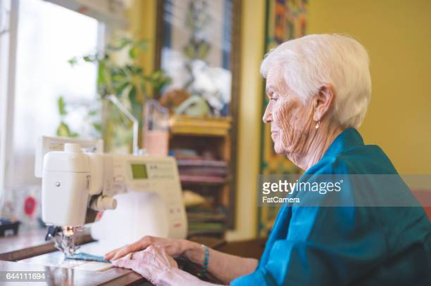 beautiful elderly woman in apartment sewing - fat granny stock pictures, royalty-free photos & images