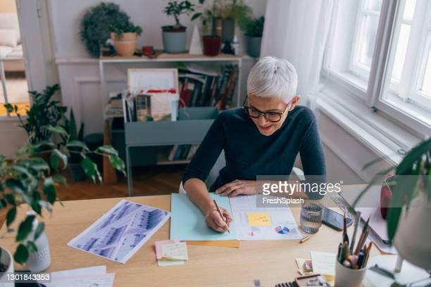 新しいプロジェクトの計画を描く美しいエレガントなシニアアーキテクト - 女性建築家 ストックフォトと画像